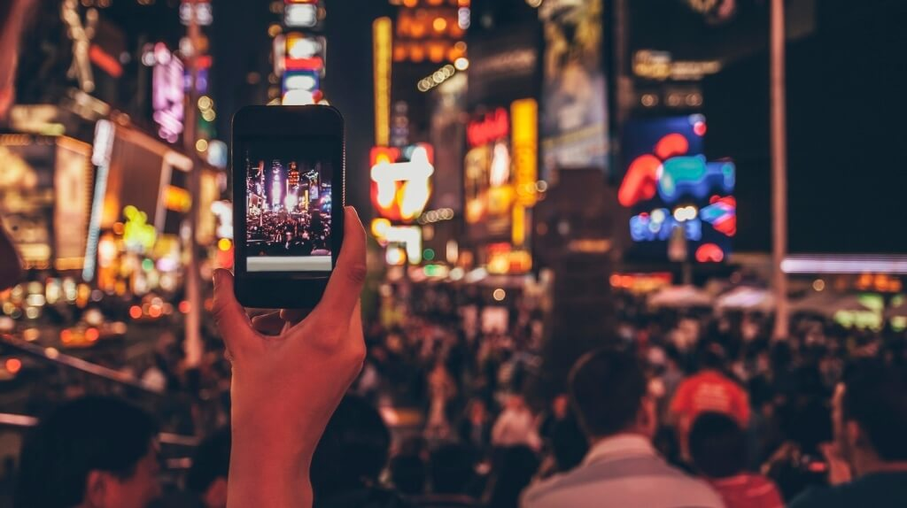 Photograph of a smartphone being used to take a photograph of a busy Times Square.